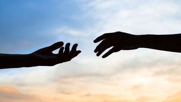 Hands_reaching_out_to_eachother.jpeg  Shadowed hands reaching out across a sunlit sky background.
