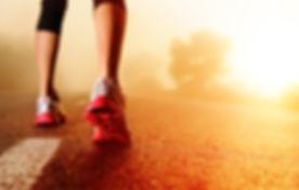 Athlete runner feet running on road clos
