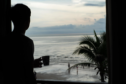 silhouette-of-man-holding-the-coffee-cup-and-looking-at-the-sea-from-the-bedroom-free-phot