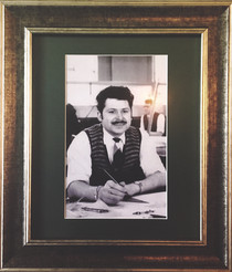 Barry at his desk. The tools he in using in the picture are now hung in a frame at the Draughtsman Alehouse.