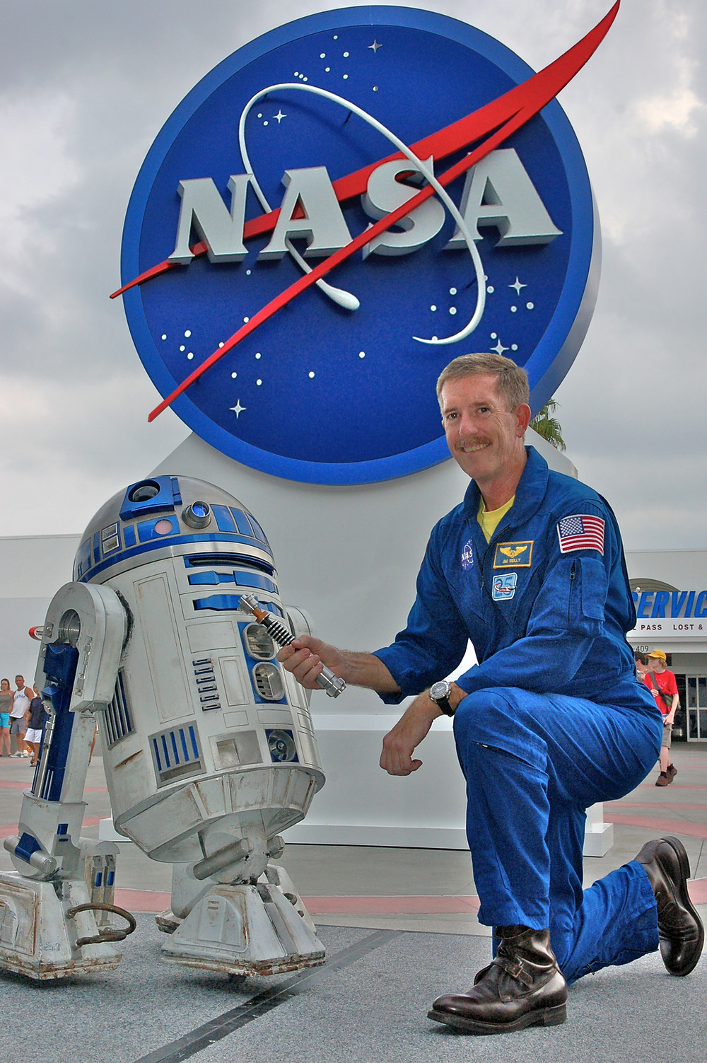 Astronaut Jim F Reilly and R2-D2 pose with a lightsaber in front of the NASA logo