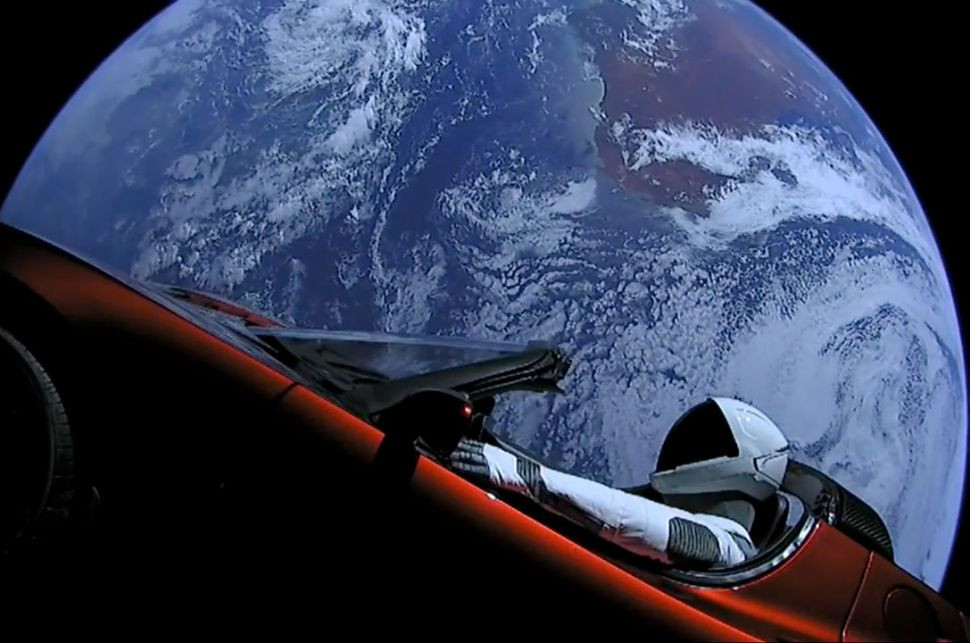 A red Tesla Roadster floating in space in front of the planet Earth with a crash test dummy in the driver's seat
