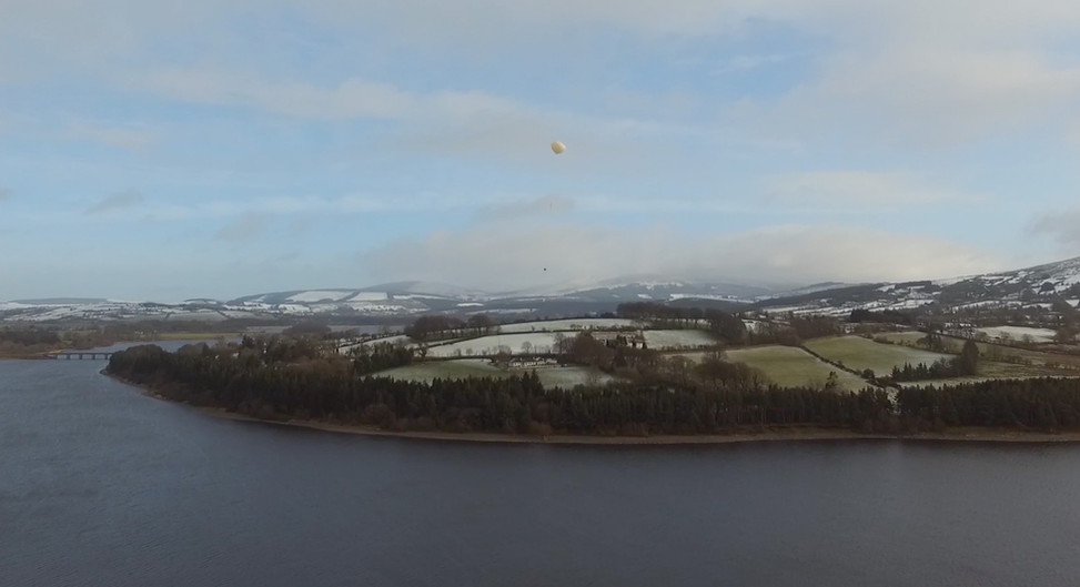 Drone over water with snowy ground.jpg