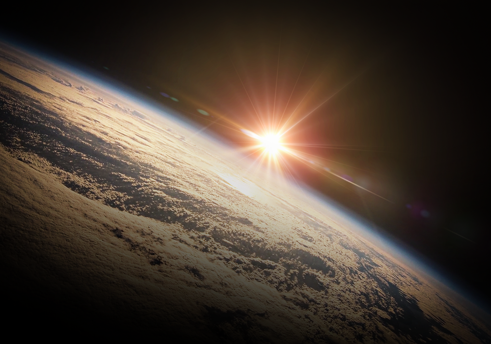 Warm glow of the sun rising over Earth with thin blue line of the atmosphere, blackness of space and beautiful cloud formations from above
