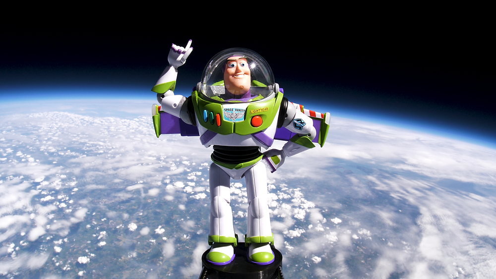 A Buzz Lightyear toy in front of the Earth and the black vacuum of space