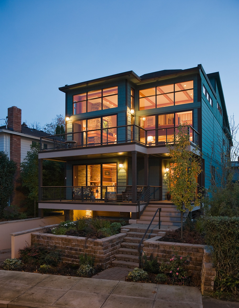 Outside of three story very modern wooden house at dusk, with the lights on in all the rooms