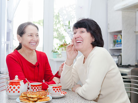 Two mature women talking over coffee in