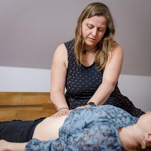 Mütterpflegerin Friederike Bandelin gibt eine Bauchmassage an eine Wöchnerin.