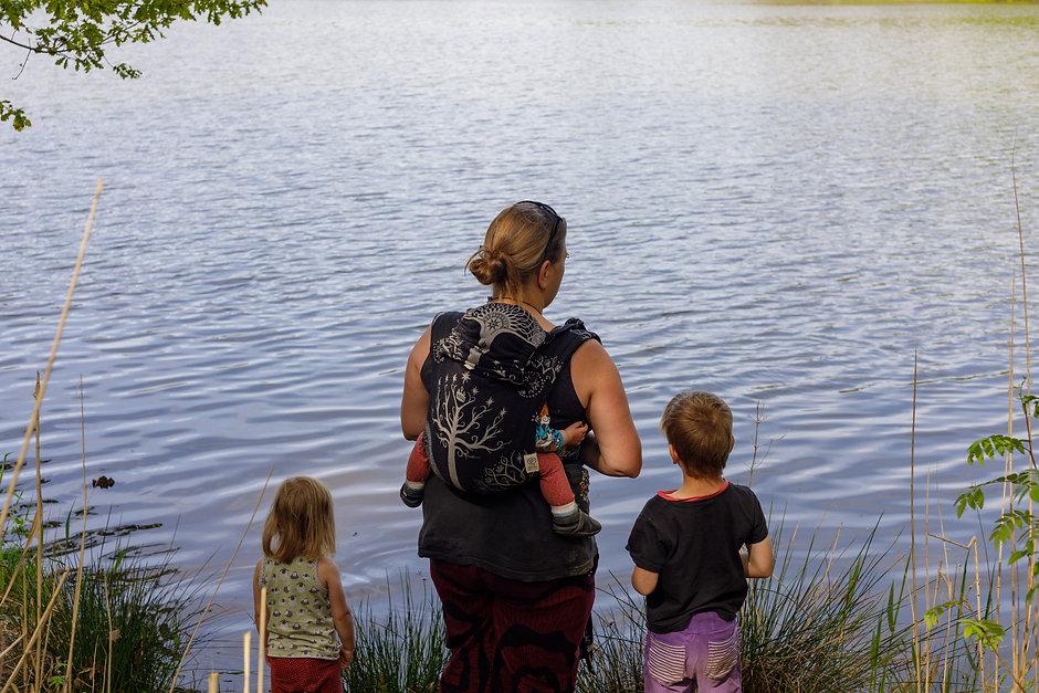 Mütterpflegerin Friederike Bandelin steht mit dem Rücken zum Betrachter und schaut auf ein Gewässer. Ein kleines Kind ist auf ihrem Rücken in einer Trage, zwei weitere Kinder stehen jeweils rechts und links von ihr und schauen ebenfalls aufs Gewässer.