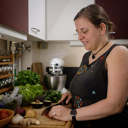 Mütterpflegerin Friederike Bandelin schneidet Gemüse auf einem Brett und ist in die Zubereitung einer Mahlzeit vertieft.