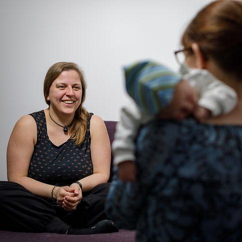 Mütterpflegerin Friederike Bandelin ist im gespräch mit einer Mutter mit Neugeborenem auf dem Arm.