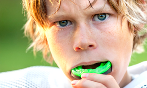 a young athlete putting a dirty mouth guard in his mouth