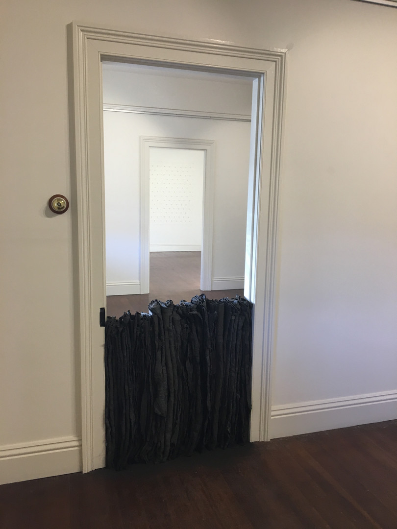 Schoolhouse Door Blockade, 2018, Fabric, cement, clay & iron oxide installation, 90x80x15cm. Behind: Ally McKay, Hold, 2018, Wall based installation