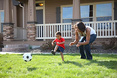 mother and son in front yard pllaying  kick ball  home warranties of virginia
