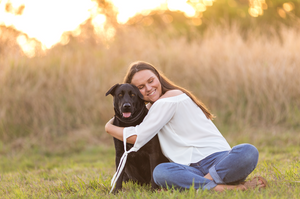 a girl hugging her black labrador during a Brisbane pet photography session