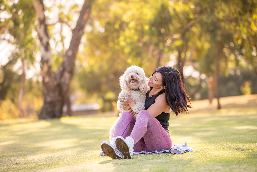 a dark haired woman in activewear is holding her fluffy dog and smiling at him. They are sitting in a park