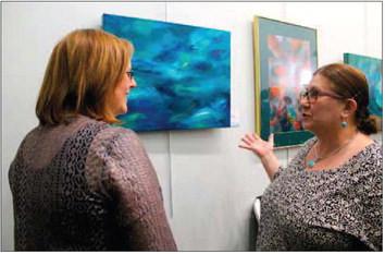 "Deanna Weinholtz, left, and Lynn Larsen, right, discuss Weinholtz's painting ""Blue Reflections."" Larsen considers herself a collector of Weinholtz's work. Photo by MIASUMMERSON/CONTRIBUTOR"