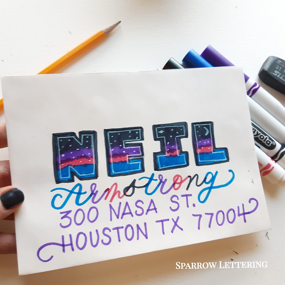 Galaxy themed envelope with Neil on the first line in block letters, Armstrong in colorful cursive on the next line, 300 Nasa Street on the 3rd line and Houston, Texas and the zip code on the 4th line.