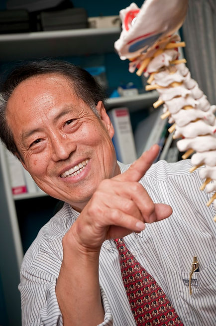 Smiling physiotherapist educating about spine