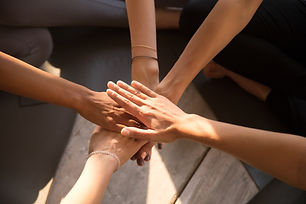 Top view of multiracial women sit in circle on training put hands in stack showing mutual