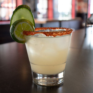 Cucumber jalapeno margarita garnished with lime and cucumber slice.