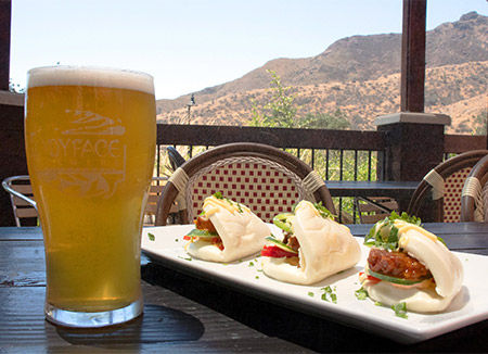 Glass of beer and plate of food served near Lake Lindero brewery.