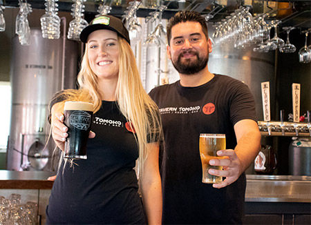 Male and female bartenders holding beer and smiling at our bar near Oak Park.