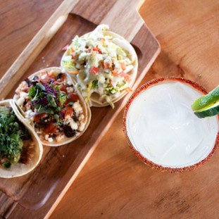 Three tacos and a drink garnished with lime slices.