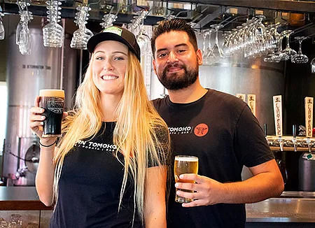 Male and female bartenders holding beer and smiling at our lunch restaurant near Old Agoura, Agoura Hills.