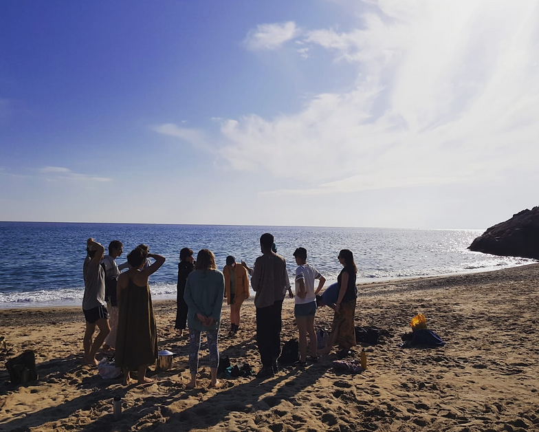 Image description: A group of ten stand in a circle on a sandy beach in Catalonia, Spain. The sun casts long shadows and the sea glistens.