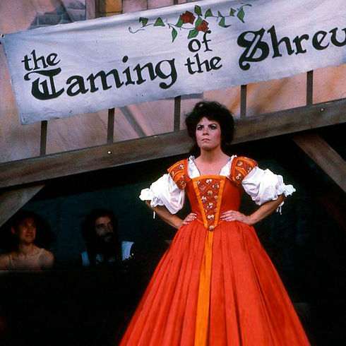 """An actor performing in Elizabethan dress standing with hands on her hips in """"Taming of the Shrew""""."""