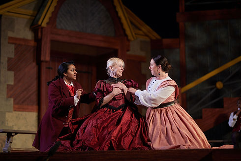 Three performers in Elizabethan dress talking to one another.
