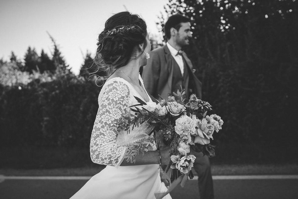 photos de mariés marchant avec le bouquet de fleurs