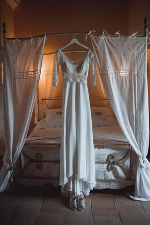 Robe de mariée suspendue sur le lit de la marié
