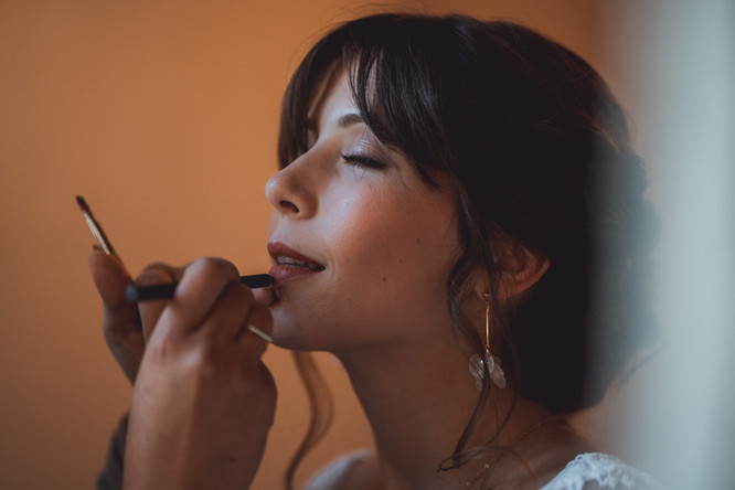 portrait de mariée qui met du rouge à lèvre