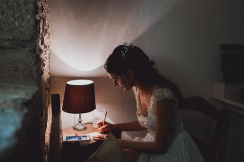 Mariée qui écrit ses voeux pendant les préparatifs