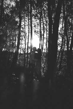 Photo en noir et blanc d'un couple en forêt dans les bois