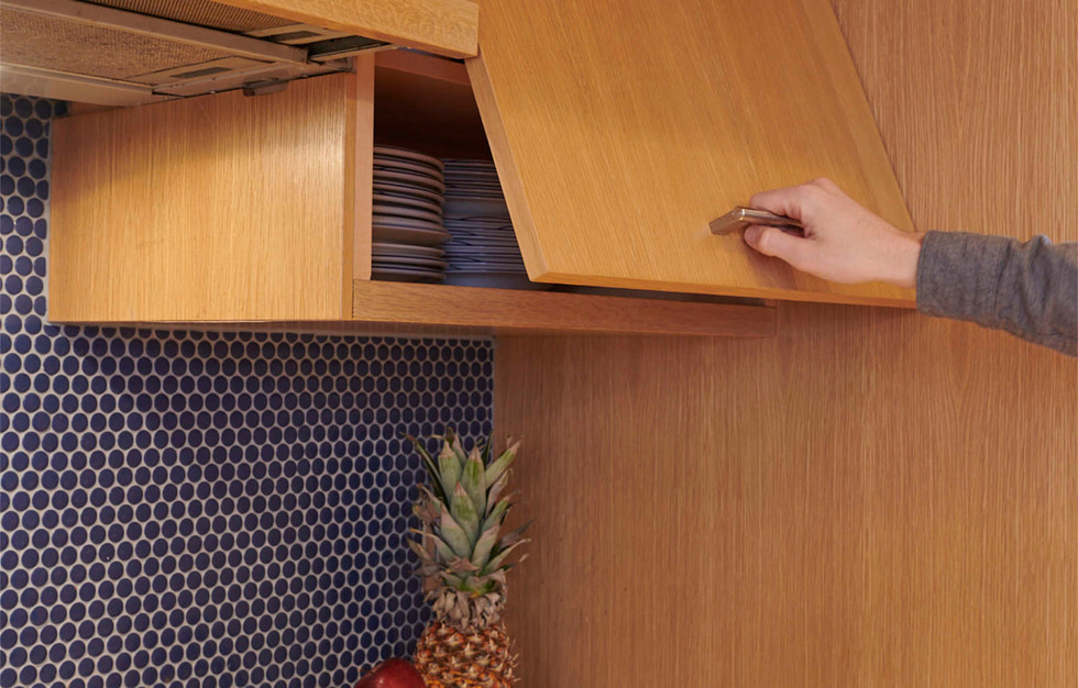 Hinged upper cabinets that swing open upward plus a slick pull-out range hood fan with lighting