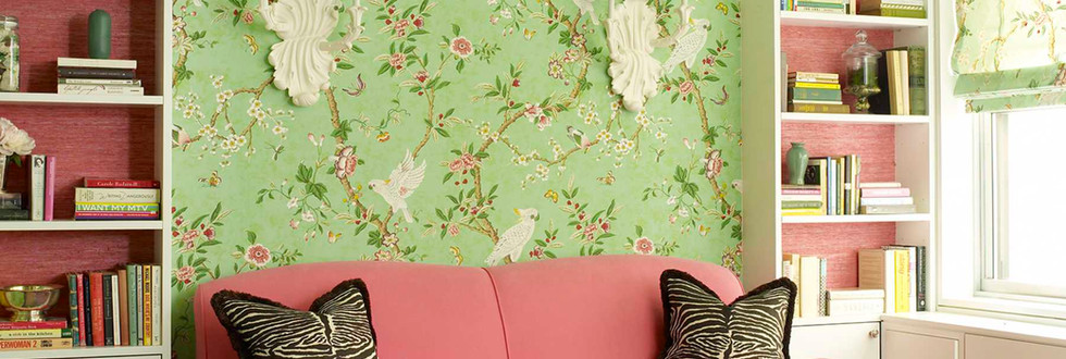 A colorful sitting area includes wallpaper-backed open cabinets flanking and bridging over the sofa