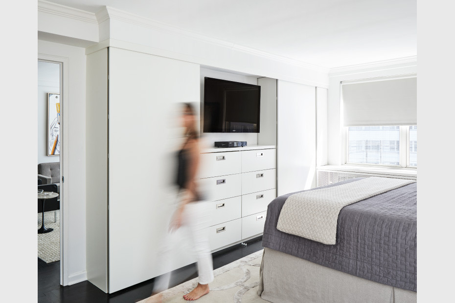 A bedroom wall unit houses a dresser and tv stand with floor-to-ceiling sliding doors in white lacquer  photo by Dylan Chandler coutesy of M Monroe Design