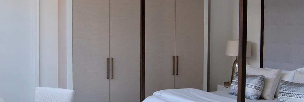 This Soho bedroom is brought to another level with svelte upholstered wardrobe cabinets