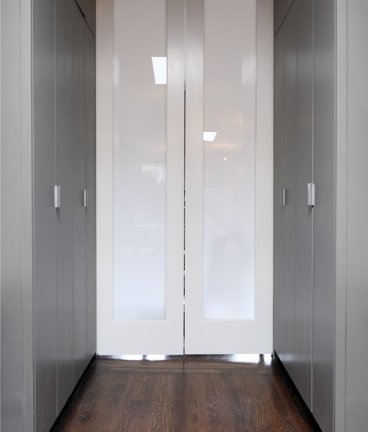 Tall flush wardrobe cabinets lead to a pair of plexi panel pocket doors creating a 'dressing room' in this East Village passageway between rooms
