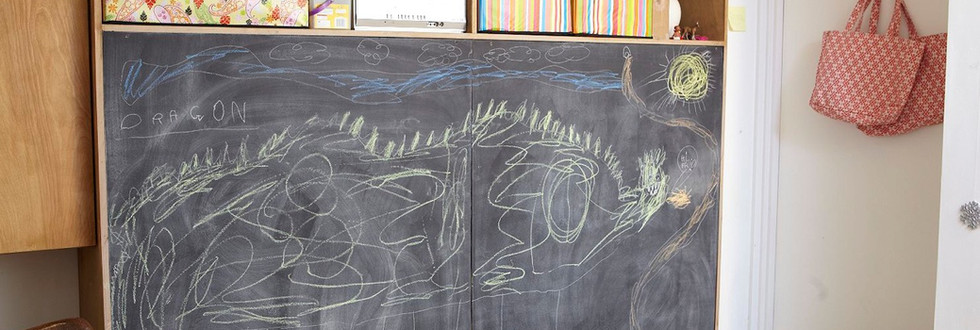 Also featuring a built-in storage cabinet (toys!) behind chalk-board painted doors