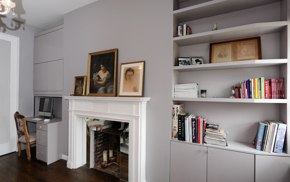 This full wall of living room cabinetry includes a built in desk with a roll down tambour door, file cabinets and closed uppers, plus a mixed use cabinet angled to allow room for a window on the far right