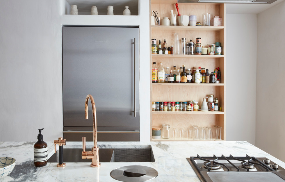 A walk in pantry for deeper storage lives behind this tall  open shelf in natural birch