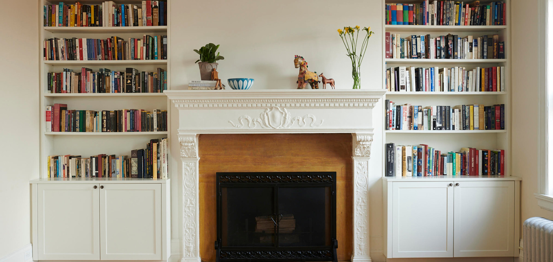 Shaker doors and integrated picture rail moulding help these bookshelf cabinets to seamlessly flank a large and ornate mantle; feeling both contemporary and traditional.