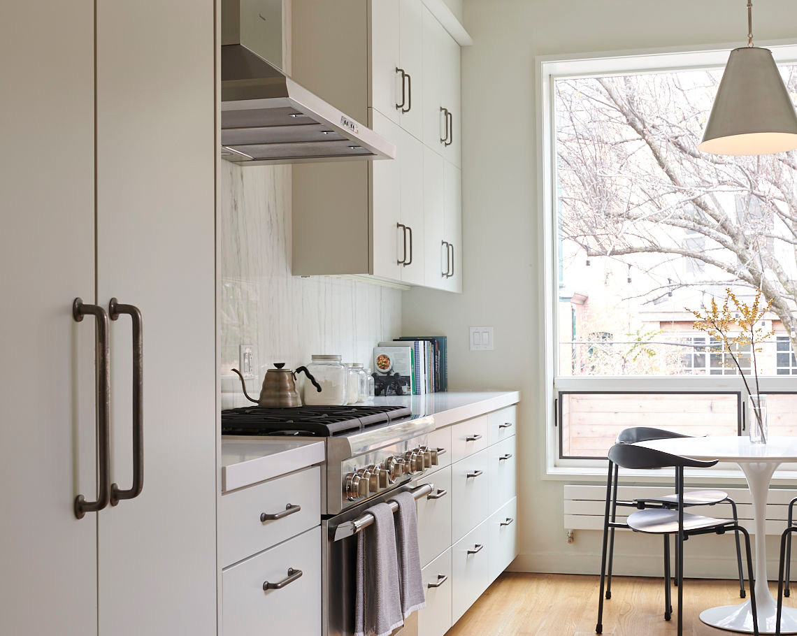 Tall pantry cabinets and built-in refrigerator with custom panels on the near end of the kitchen