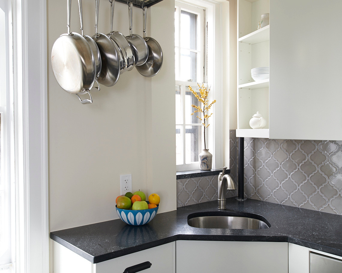 A corner sink and angled upper cabinet allowing window light were two solutions for best using the available space