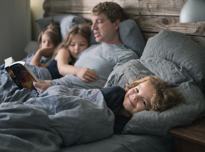 Family in bed reading together