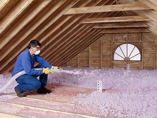 Image of man working on insulation in an attic